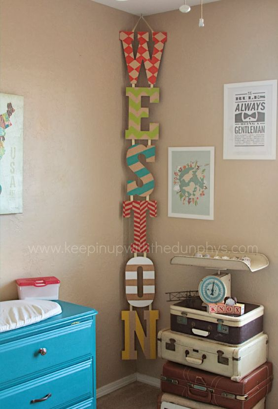 Painted Name Letters Hung Vertically In The Corner.