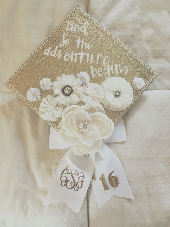 Graduation Cap Decorated With White Faux Flowers and Pearls.