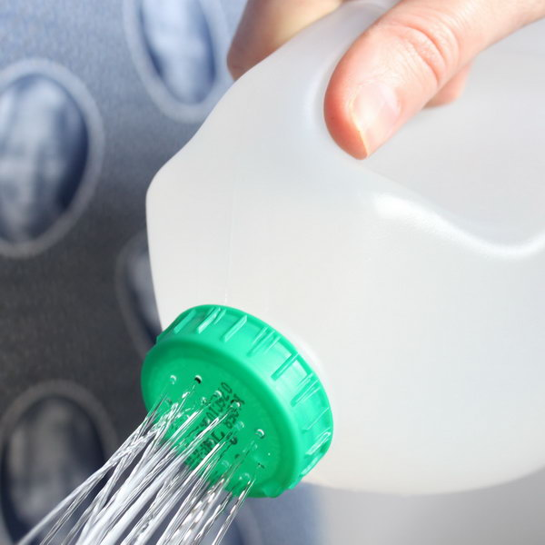 Make holes in the top of a used milk bottle for DIY watering can.